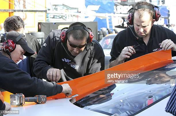 Crew members of the Home Depot Toyota make adjustments to the deck spoiler during Daytona Preseason Thunder at Daytona International Speedway on...