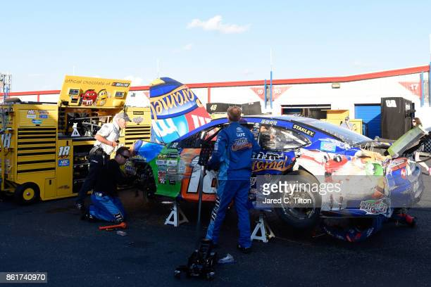 Crew members of the MM's Caramel Toyota driven by Kyle Busch push the car in the garage area after an ontrack incident during the Monster Energy...