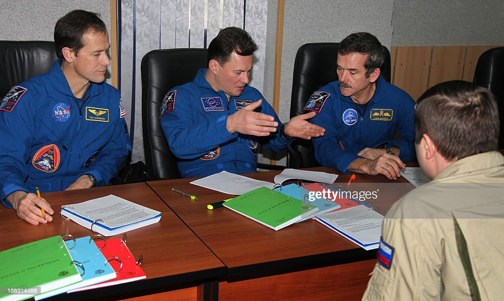 Crew members of the next expedition to the International Space Station (back R-L), Canadian astronaut Chris Hadfield, Russian cosmonaut Roman Romanenko and US astronaut Tom Marshburn, take part in the preflight preparation at the Russian leased Kazakhstan's Baikonur cosmodrome on December 13, 2012. Hadfield, Romanenko and Marshburn will join in December the remaining ISS crew, Russians Oleg Novitskiy and Evgeny Tarelkin, and Kevin Ford of the United States, who arrived there last month.