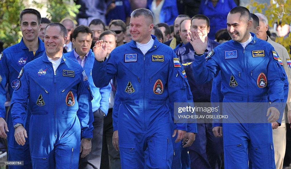 Crew members of the next expedition to the International Space Station (ISS), (L-R) US astronaut Kevin Ford, Russian cosmonauts Oleg Novitskiy and Evgeny Tarelkin walk to a bus during a sending-off ceremony in the Russian-leased Baikonur cosmodrome on October 23, 2012. The crew is to blast off for the International Space Station in a Russian Soyuz space craft.