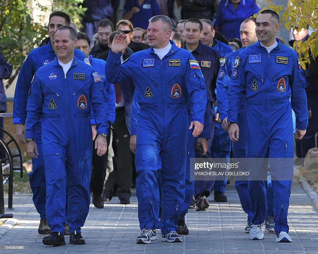 Crew members of the next expedition to the International Space Station (ISS), (L-R) US astronaut Kevin Ford, Russian cosmonauts, Oleg Novitskiy and Evgeny Tarelkin walk to a bus during a sending-off ceremony in the Russian-leased Baikonur cosmodrome on October 23, 2012. The crew is to blast off for the International Space Station in a Russian Soyuz space craft.