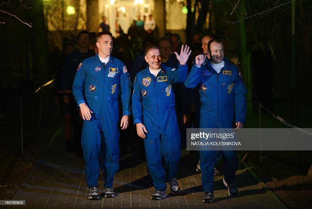 Crew members of the next expedition to the International Space Station (ISS), (L-R) US astronaut Christopher Cassidy, Russian cosmonauts, Pavel Vinogradov and Alexander Misurkin walk from their hotel to a bus during a sending-off ceremony in the Russian-leased Baikonur cosmodrome on March 28, 2013. The launch of the Soyuz TMA- 08M spacecraft with Cassidy, Vinogradov and Misurkin aboard is scheduled on March 29, 2013. AFP PHOTO