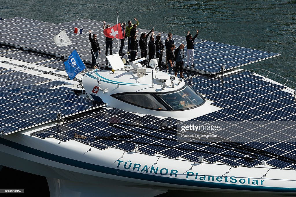 Crew members of the Turanor PlanetSolar, largest solar vessel in the world powered exclusively by the sun, wave to the crowd as they depart to Lorient on September 15, 2013 in Paris, France. The vessel now docked in the River Seine has been gathering data in the Gulf Stream for five months on oceanic processes interacting with the atmosphere.