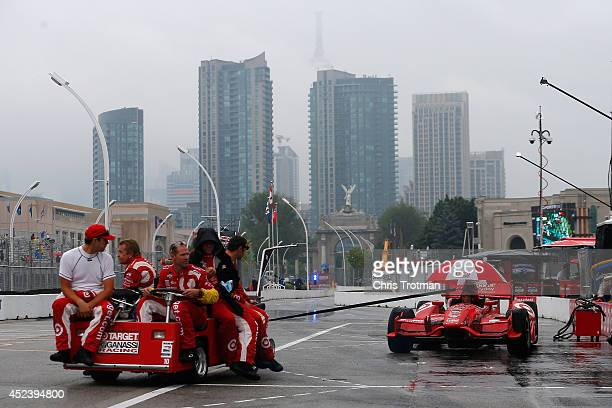 Crew members of Tony Kanaan of Brazil driver of the Target Chip Ganassi Racing Dallara Honda roll the car out of pit lane after the race was canceled...