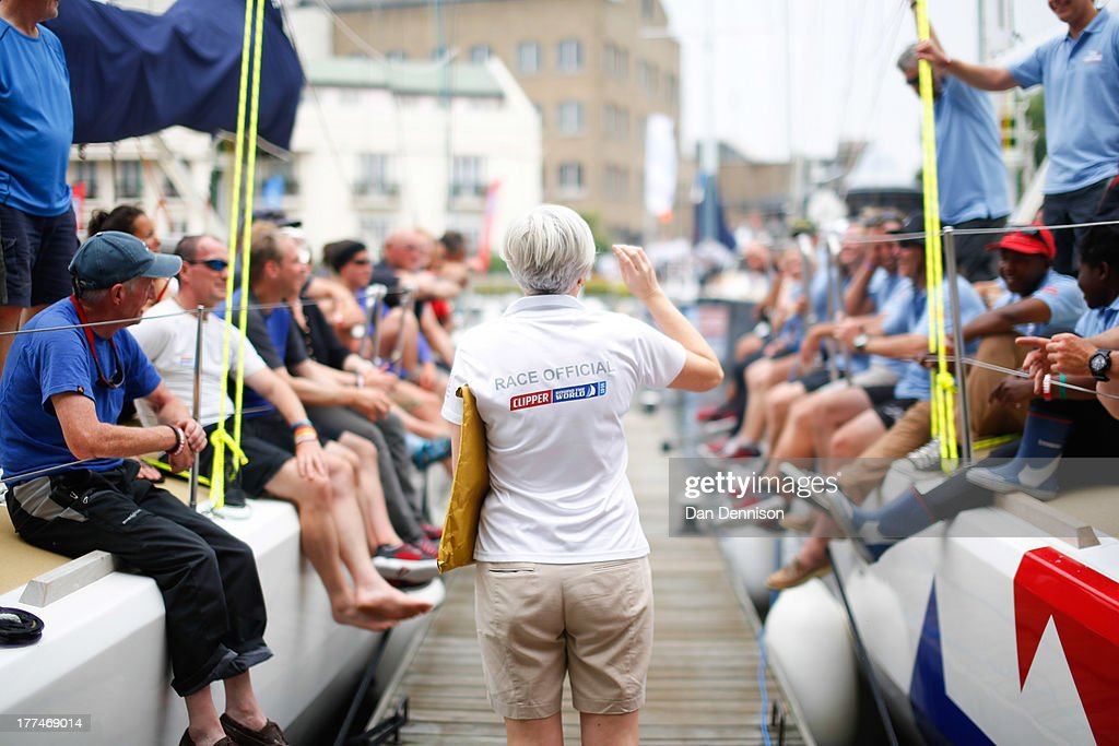 Crew members of two of the race yachts competing in The Clipper 2013-14 Round The World Yacht Race, listen to a race offical in St Katherine's Dock, east London on August 23, 2013. The 40,000 mile, 8-leg course begins on September 1 and will visit six continents, taking eleven months to complete.