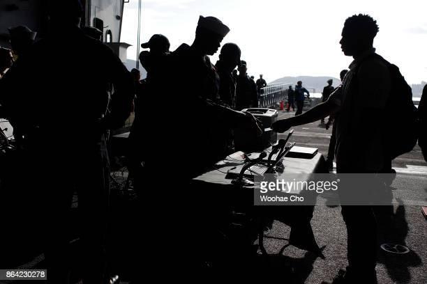 Crew members of US aircraft carrier Ronald Reagan undergo security checks in a hangar bay before disembarking at Busan Naval base on October 21 2017...