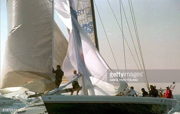 Crew members on the foredeck of Stars and Stripes hoist a gennaker with Dennis Conner at the helm as they round the first mark to sail the downwind...