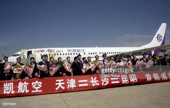 Crew members pose for pictures in front of Okay Airlines' first flight during a ceremony after the plane arrived at Kunming Wujiaba Airport on March...