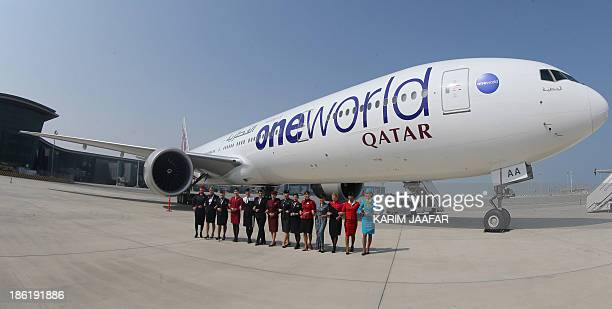 Crew members pose in front of an aircraft during a ceremony to mark the alliance of Qatar Airways and Oneworld airline grouping on October 29 2013 at...