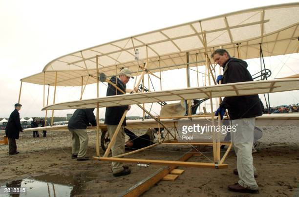 Crew members prepare a replica of the 1903 Wright Flyer prior to an unsuccessful reenactment of the Wright brothers' first flight during Centennial...