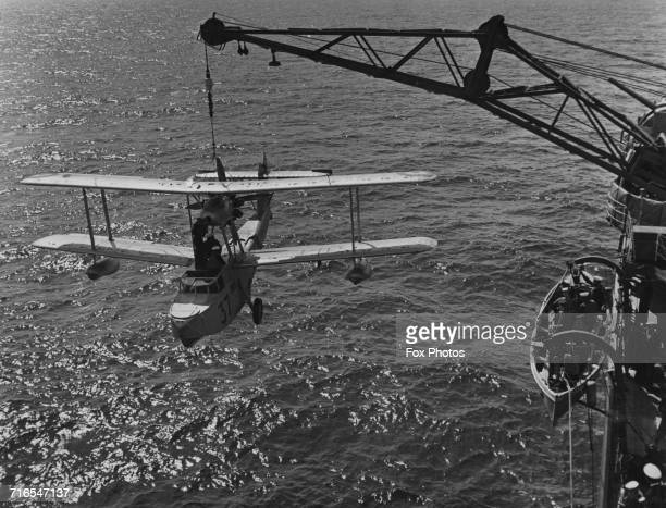 Crew members prepare to hoist their Supermarine Walrus singleengine amphibious biplane reconnaissance aircraft seaplane from No 9 Squadron RAAF back...