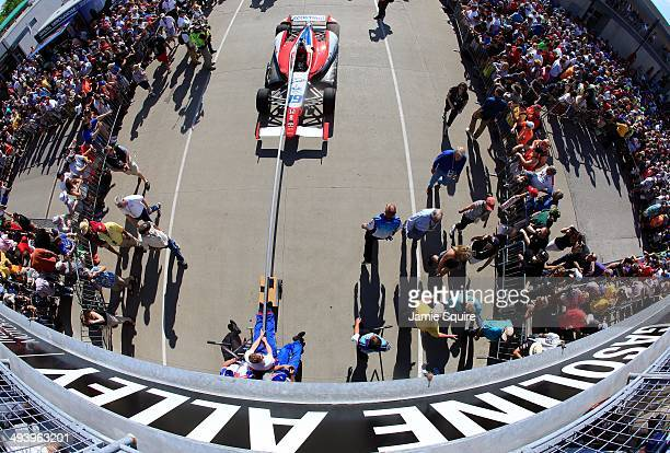 Crew members pull the car of Justin Wilson of England driver of the Dale Coyne Racing Honda Dallara through gasoline alley toward the grid prior to...