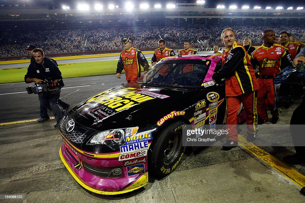 Crew members push the #15 5-Hour Energy Benefiting Avon Foundation for Women Toyota of Clint Bowyer to Victory Lane after Bowyer ran out of fuel after winning the NASCAR Sprint Cup Series Bank of America 500 at Charlotte Motor Speedway in Concord, North Carolina.