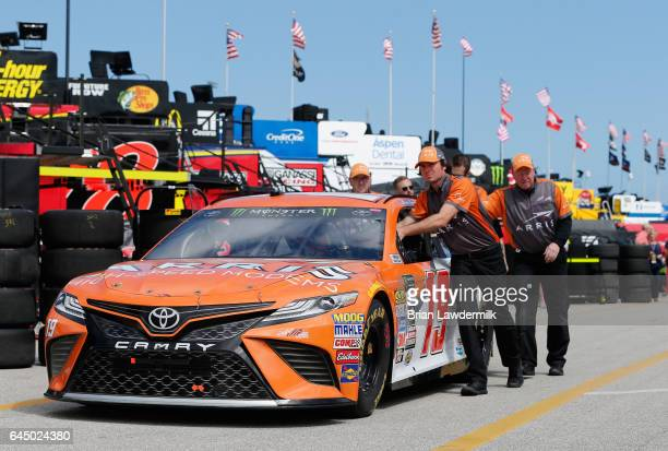 Crew members push the ARRIS Toyota driven by Daniel Suarez through the garage area during practice for the 59th Annual DAYTONA 500 at Daytona...