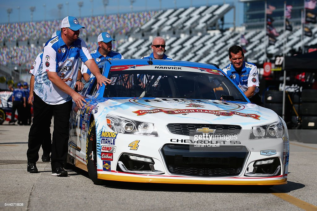Crew members push the #4 Busch Beer Chevrolet driven by Kevin Harvick through the garage area during practice for the NASCAR Sprint Cup Series Coke Zero 400 at Daytona International Speedway on July 1, 2016 in Daytona Beach, Florida.