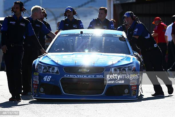 Crew members push the car of Jimmie Johnson driver of the Lowe's Chevrolet in the garage area during practice for the NASCAR Sprint Cup Series...