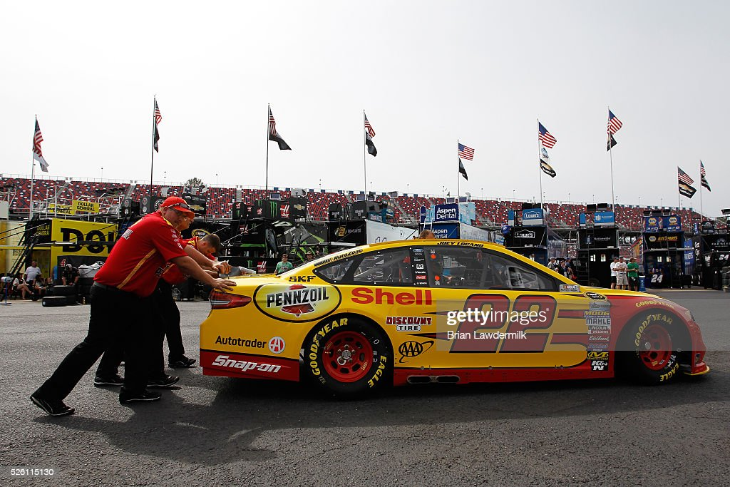 Crew members push the car of Joey Logano, driver of the #22 Shell Pennzoil Ford, through the garage area during practice for the NASCAR Sprint Cup Series GEICO 500 at Talladega Superspeedway on April 29, 2016 in Talladega, Alabama.
