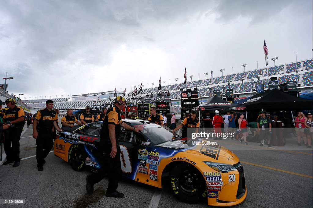 Crew members push the car of <a gi-track='captionPersonalityLinkClicked' href=/galleries/search?phrase=Matt+Kenseth&family=editorial&specificpeople=204192 ng-click='$event.stopPropagation()'>Matt Kenseth</a>, driver of the #20 DeWalt Toyota, through the garage area during practice for the NASCAR Sprint Cup Series Coke Zero 400 at Daytona International Speedway on June 30, 2016 in Daytona Beach, Florida.