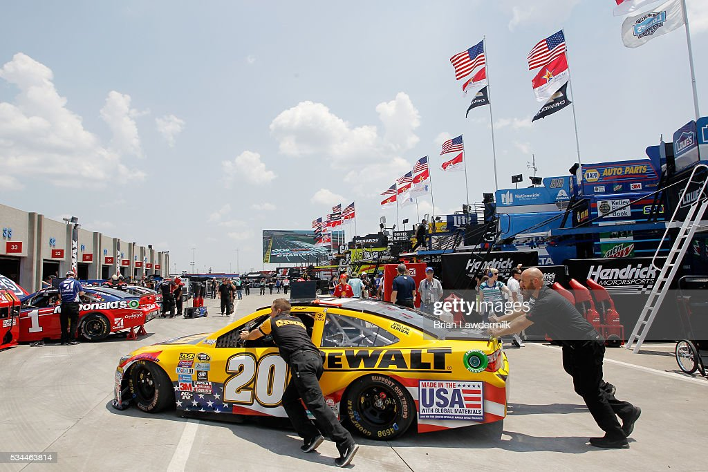 Crew members push the #20 DeWalt Toyota, driven by Matt Kenseth, through the garage area during practice for the NASCAR Sprint Cup Series Coca-Cola 600 at Charlotte Motor Speedway on May 27, 2016 in Charlotte, North Carolina.