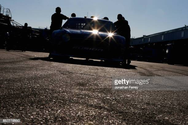 Crew members push the Ford EcoBoost Ford driven by Matt DiBenedetto through the garage area during practice for the Monster Energy NASCAR Cup Series...