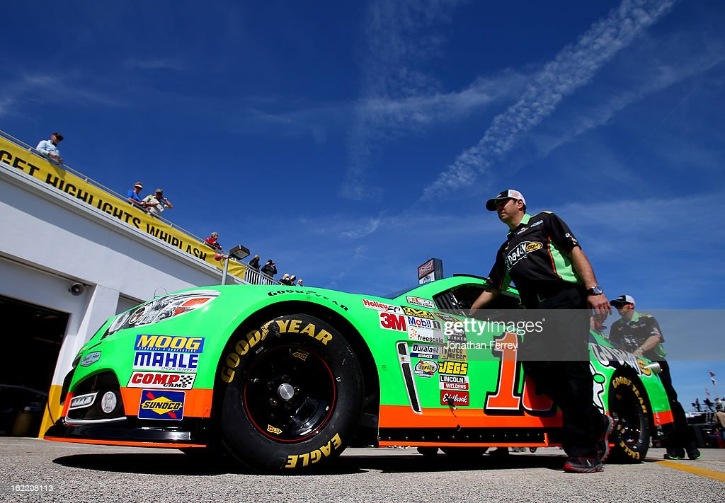 Crew members push the #10 GoDaddy.com Chevrolet, driven by Danica Patrick, through the garage area during practice for the NASCAR Sprint Cup Series Daytona 500 at Daytona International Speedway on February 20, 2013 in Daytona Beach, Florida.