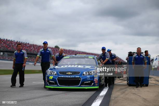Crew members push the Lowe's Chevrolet driven by Jimmie Johnson down pit road during qualifying for the Monster Energy NASCAR Cup Series Alabama 500...