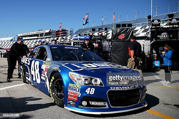 Crew members push the Lowe's Chevrolet through the garage area during practice for the 57th Annual Daytona 500 at Daytona International Speedway on...