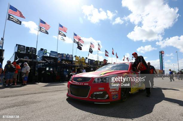 Crew members push the McDonald's Chevrolet of Jamie McMurray in the garage area during practice for the Monster Energy NASCAR Cup Series Championship...