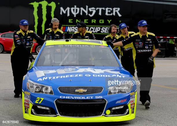 Crew members push the Menards/Peak Chevrolet driven by Paul Menard through the garage during practice for the Monster Energy NASCAR Cup Series 59th...