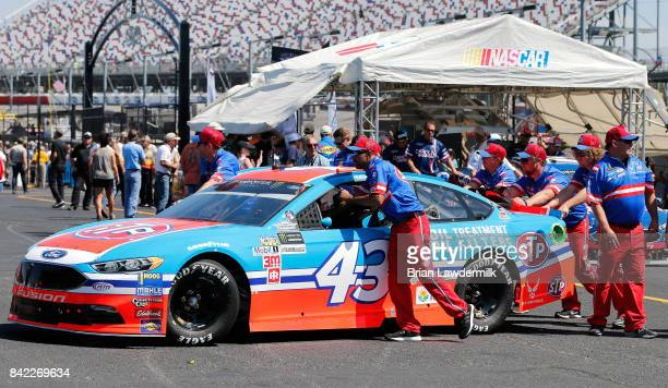 Crew members push the STP Ford driven by Aric Almirola through the garage area prior to the Monster Energy NASCAR Cup Series Bojangles' Southern 500...