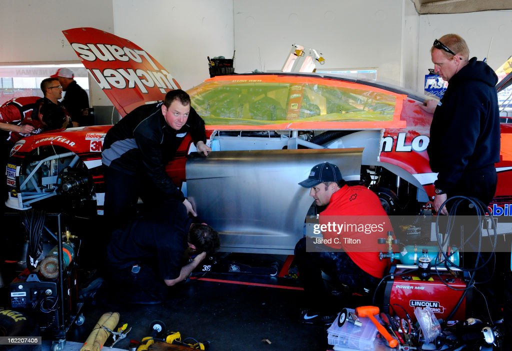 Crew members repair the #39 Quicken Loans Chevrolet of Ryan Newman in the garage area during practice for the NASCAR Sprint Cup Series Daytona 500 at Daytona International Speedway on February 20, 2013 in Daytona Beach, Florida.