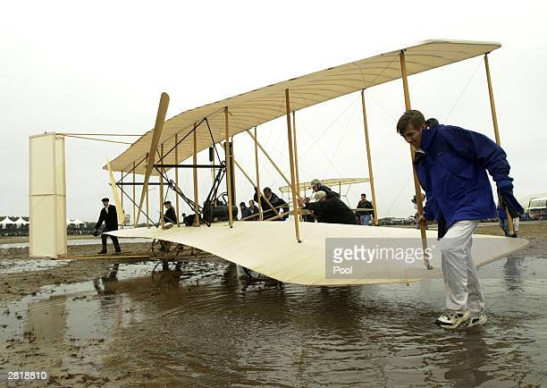 Crew members roll out the replica of the 1903 Wright Flyer prior to an unsuccessful reenactment of the Wright brothers' historic first flight during...