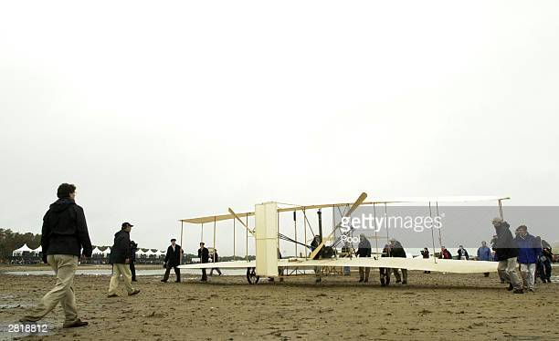 Crew members roll the replica of the 1903 Wright Flyer back to its tent after an unsuccessful reenactment of the Wright brothers' historic first...