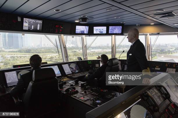 Crew members sit and stand inside the control room aboard the Genting Hong Kong Ltd Genting Dream cruise ship berthed at the Marina Bay Sands Cruise...