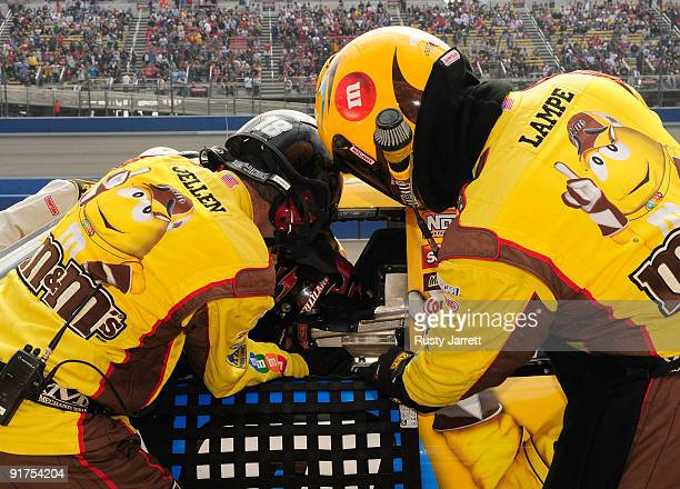 Crew members strap David Gilliland in the MM's Toyota after relieving Kyle Busch during the NASCAR Sprint Cup Series Pepsi 500 at Auto Club Speedway...