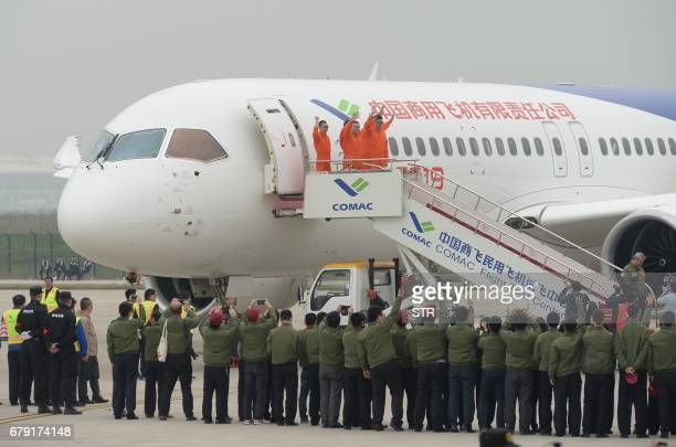 Crew members wave after completing the maiden flight of China's homegrown C919 passenger jet at Pudong International Airport in Shanghai on May 5...