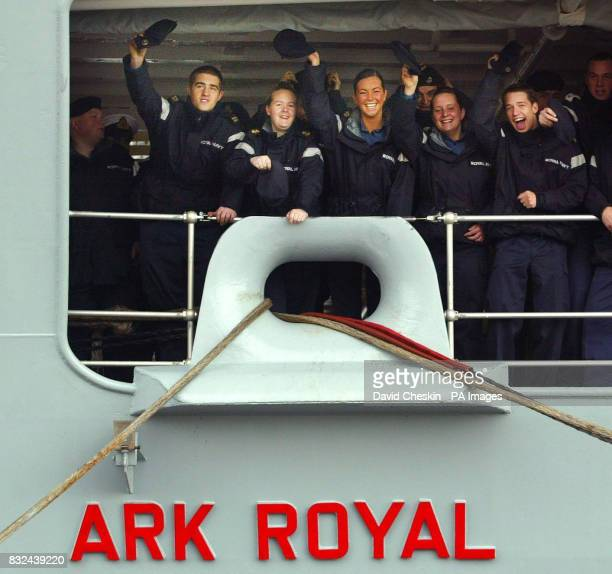 Crew members wave goodbye from the deck of the HMS Ark Royal as the ship prepares to leave Rosyth dockyard for sea trials