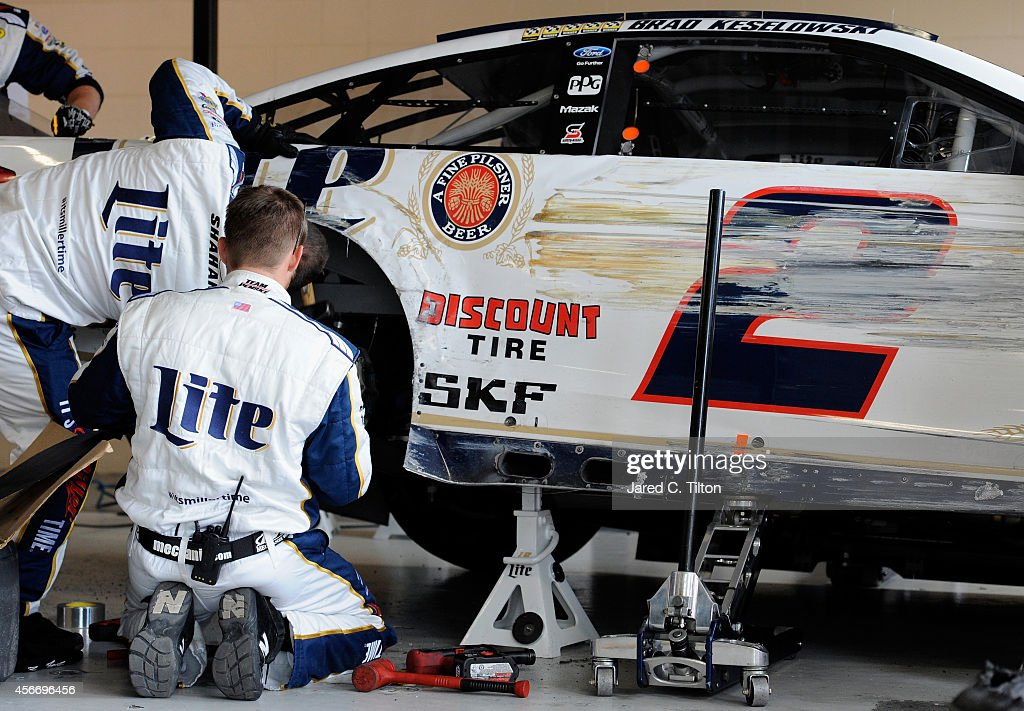 Crew members work in the garage on the car of <a gi-track='captionPersonalityLinkClicked' href=/galleries/search?phrase=Brad+Keselowski&family=editorial&specificpeople=890258 ng-click='$event.stopPropagation()'>Brad Keselowski</a>, driver of the #2 Miller Lite Ford, after crashing due to a tire failure during the NASCAR Sprint Cup Series Hollywood Casino 400 at Kansas Speedway on October 5, 2014 in Kansas City, Kansas.