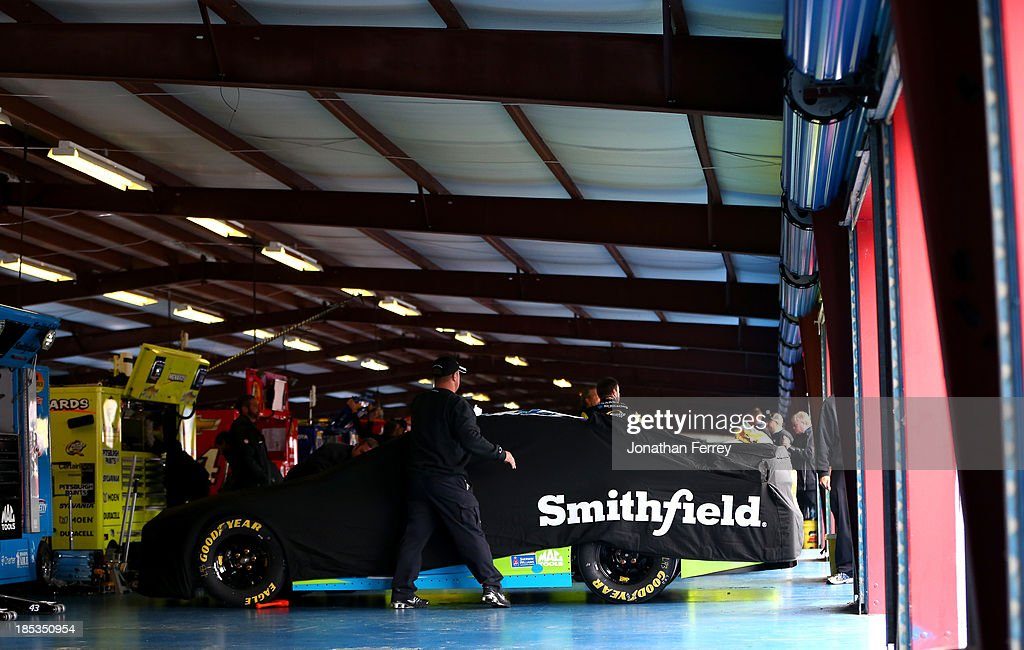 Crew members work on the car of Aric Almirola, driver of the #43 Charter Ford, in the garage after rain cancelled qualifying for the NASCAR Sprint Cup Series 45th Annual Camping World RV Sales 500 at Talladega Superspeedway on October 19, 2013 in Talladega, Alabama. Almirola was awarded the pole position after being the fastest in the first Sprint Cup practice.