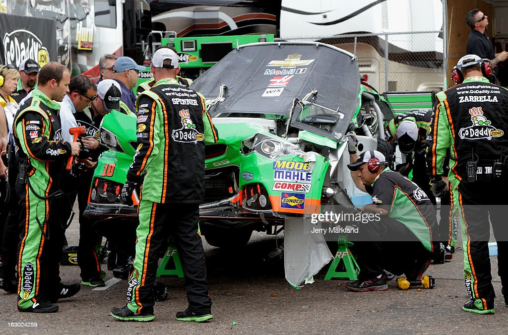 Crew members work on the car of Danica Patrick driver of the GoDaddycom Chevrolet after she wrecked during the NASCAR Sprint Cup Series Subway Fresh...