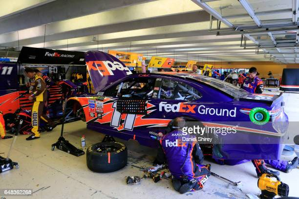Crew members work on the car of Denny Hamlin driver of the FedEx Ground Toyota in the garage after an incident during the Monster Energy NASCAR Cup...