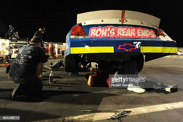 Crew members work on the car of Rich DeLong III driver of the Country Girl Saloon Chevrolet in the garage area during the NASCAR KN Pro Series West...