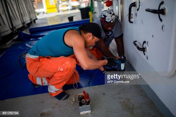 Crew members work on the deck aboard the Aquarius rescue ship on August 14 2017 in the Mediterranean Sea some 20 nautical miles from the Libyan coast...