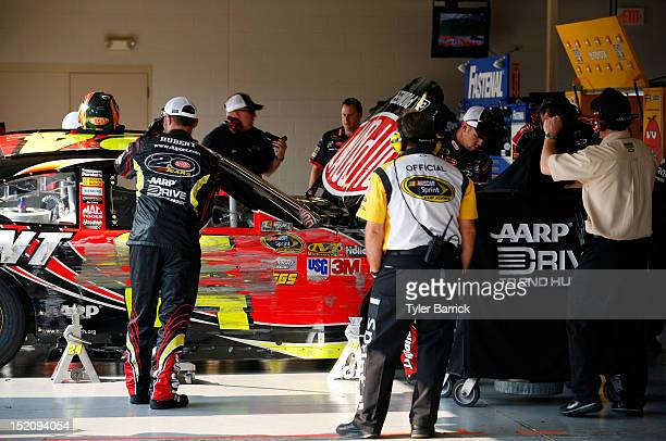 Crew members work on the DuPont Chevrolet driven by Jeff Gordon in the garage after it hit the wall during the NASCAR Sprint Cup Series GEICO 400 at...