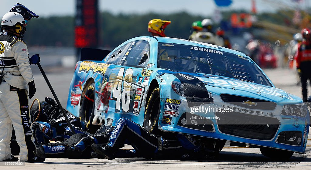Crew members work on the #48 Lowe's Planes Chevrolet, driven by <a gi-track='captionPersonalityLinkClicked' href=/galleries/search?phrase=Jimmie+Johnson+-+Nascar+Race+Driver&family=editorial&specificpeople=171519 ng-click='$event.stopPropagation()'>Jimmie Johnson</a>, following an incident during the NASCAR Sprint Cup Series GoBowling.com 400 at Pocono Raceway on August 4, 2013 in Long Pond, Pennsylvania.