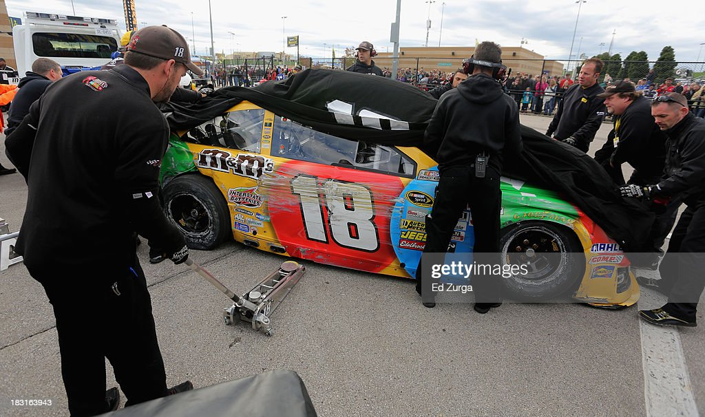 Crew members work on the #18 M&M's Toyota of Kyle Busch in the garage area after an on track incident during practice for the NASCAR Sprint Cup Series 13th Annual Hollywood Casino 400 at Kansas Speedway on October 5, 2013 in Kansas City, Kansas.