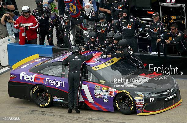 Crew members work on the roof flap of Denny Hamlin driver of the FedEx Freight Toyota during the NASCAR Sprint Cup Series CampingWorldcom 500 at...