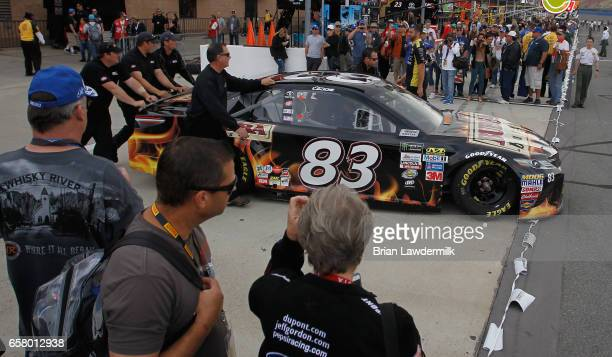 Crew memebers push the car od Corey LaJoie driver of the Bubba Burger Toyota on to pit lane before the Monster Energy NASCAR Cup Series Auto Club 400...