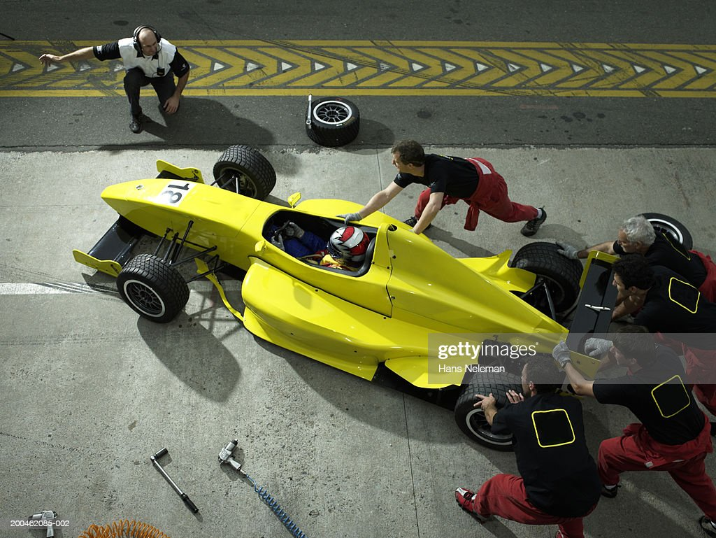 Crew pushing Formula 1 racer back out of pit, elevated view : Stock Photo