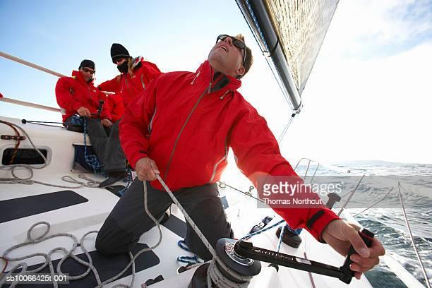 Crew sailing racing yacht